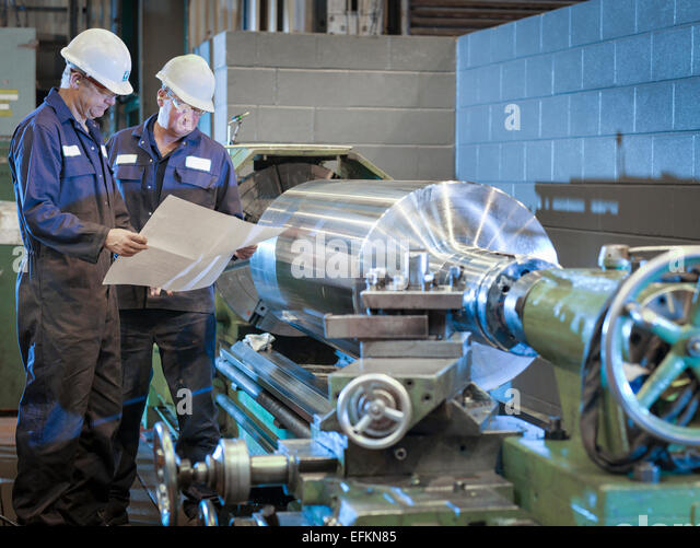 Engineers working with drawings on lathe - Stock-Bilder