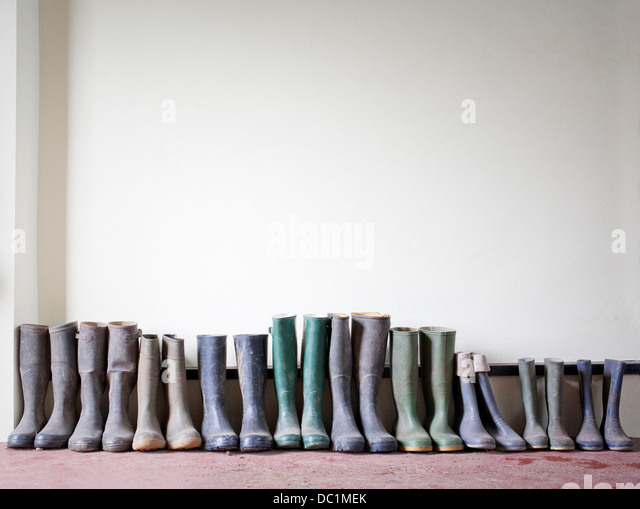 Rubber boots in a row - Stock Image
