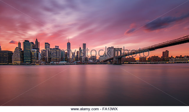 The Manhattan skyline with its skyscrapers and Brooklyn Bridge at sunset with beautiful pink and orange clouds and - Stock Image