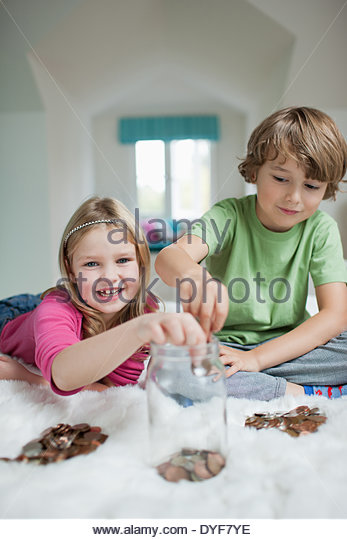 Brother sister playing counting money in bedroom - Stock Image