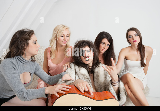 Young male guitarist with a cool gesture amid female group - Stock-Bilder