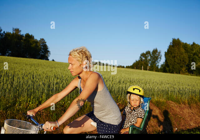 Woman with daughter (4-5) riding bike - Stock Image