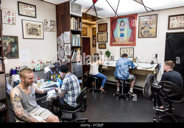 Manhattan New York City NYC NY Chinatown Daredevil Tattoo Shop workbench artist drawing artwork display customer - Stock Image