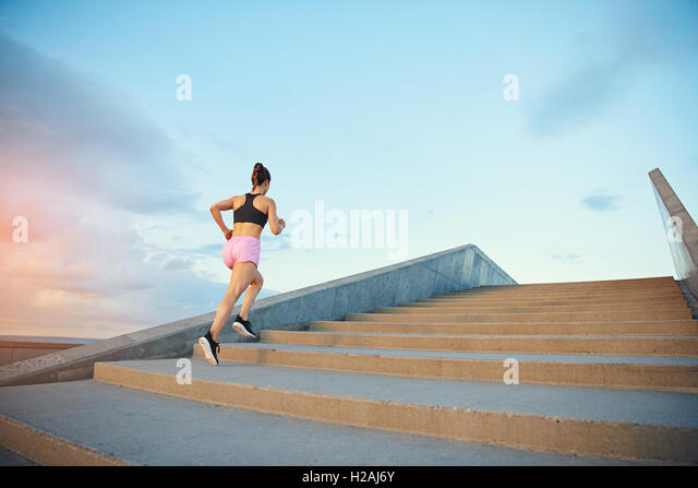Low angle view of a fit healthy young woman jogging up a flight of outdoor concrete stairs at sunrise in an active - Stock Image