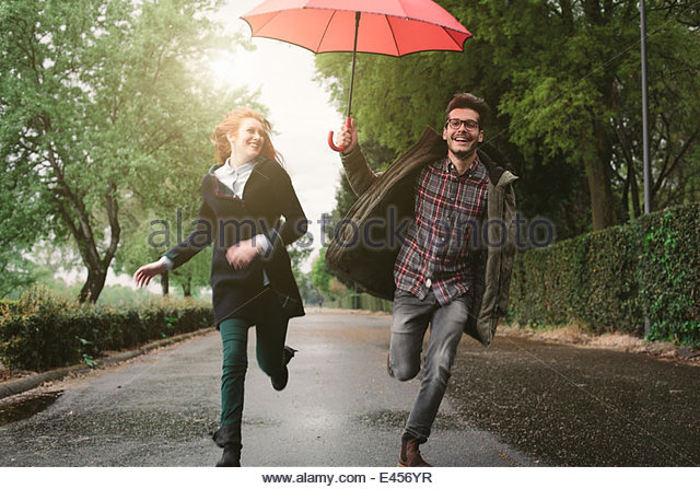 Couple running in park under umbrella - Stock-Bilder