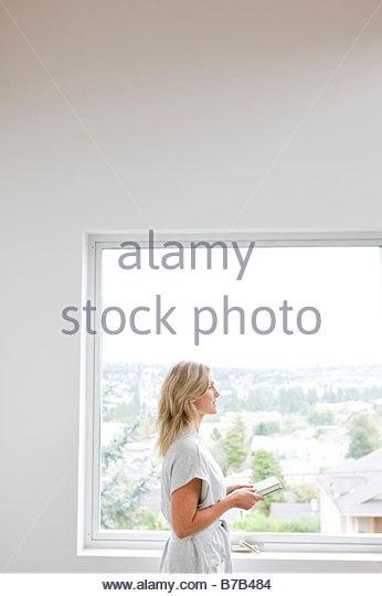 Woman walking past window with book - Stock-Bilder