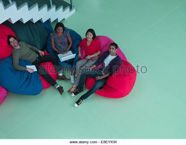 Smiling business people sitting in bean bag chairs - Stock-Bilder