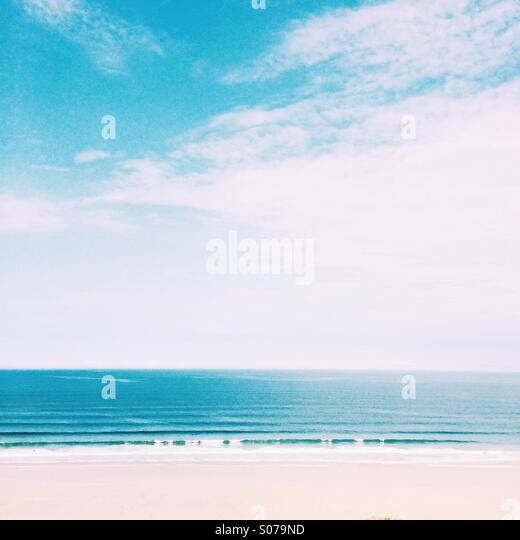 Waves rolling into the beach in summer - Stock Image