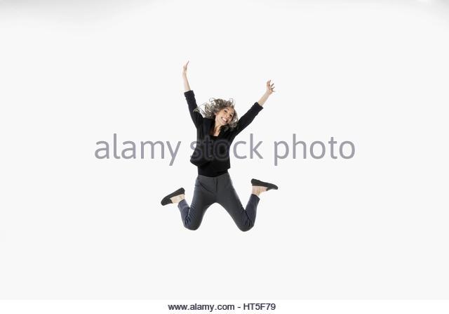 Exuberant woman jumping for joy against white background - Stock-Bilder