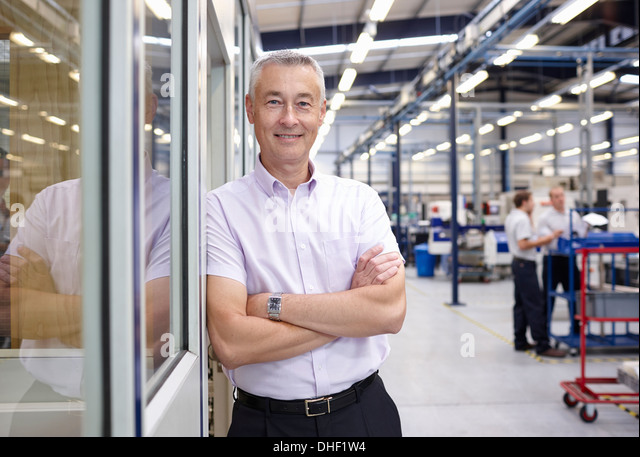Portrait of manager with arms folded in engineering factory - Stock Image