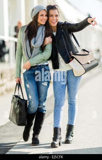 Two young beautiful women walking and shopping with joyful expressions - Stock Image