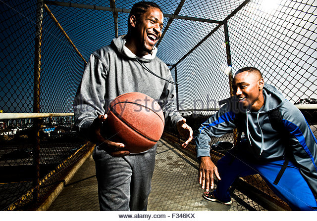 Two friends play around with a basketball - Stock Image