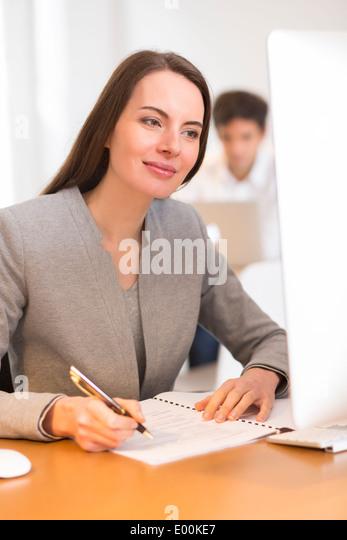 Pretty woman desk computer background colleague - Stock Image