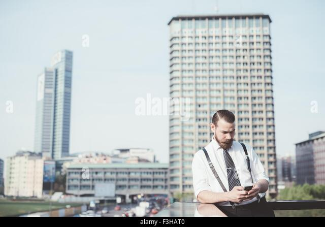 Stylish businessman reading smartphone text update on office balcony - Stock Image