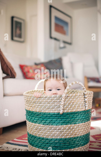 Baby sitting in basket - Stock Image