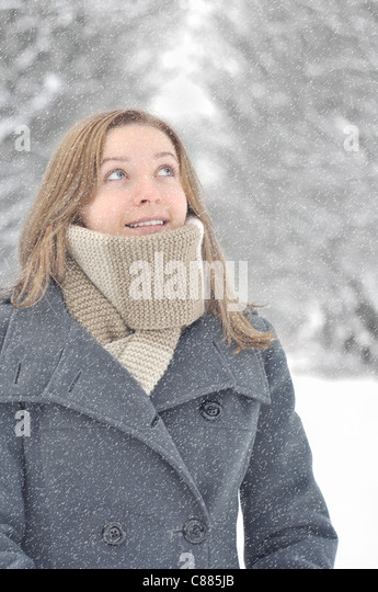 Young smiling winter woman under the snow - Stock Image