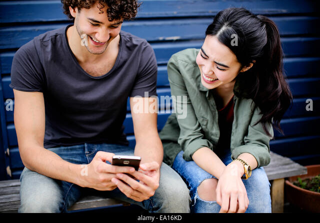 Couple laughing at phone message - Stock Image