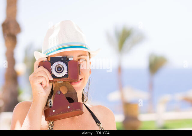 Young girl taking photos with old film camera on summer vacation. Holidays tourism background - Stock-Bilder