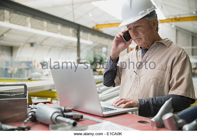 Worker at laptop in manufacturing plant - Stock-Bilder