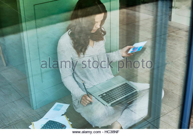 Mid adult woman working from home. - Stock Image