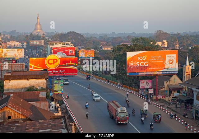 Traffic in street with billboards in the city Bago, formerly Pegu, Bago Region, Myanmar / Burma - Stock Image