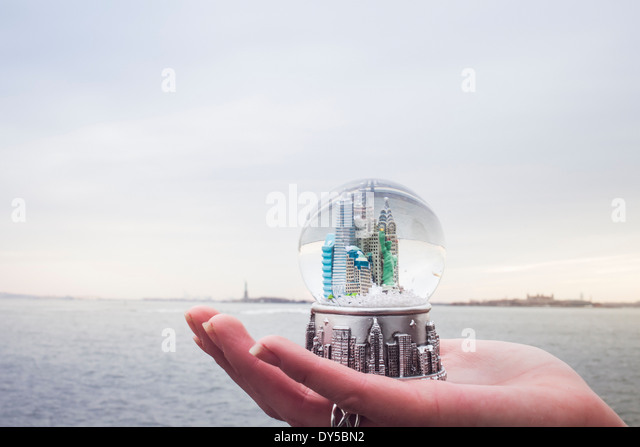 Young woman's hand holding landmark snowglobe, New York, USA - Stock-Bilder