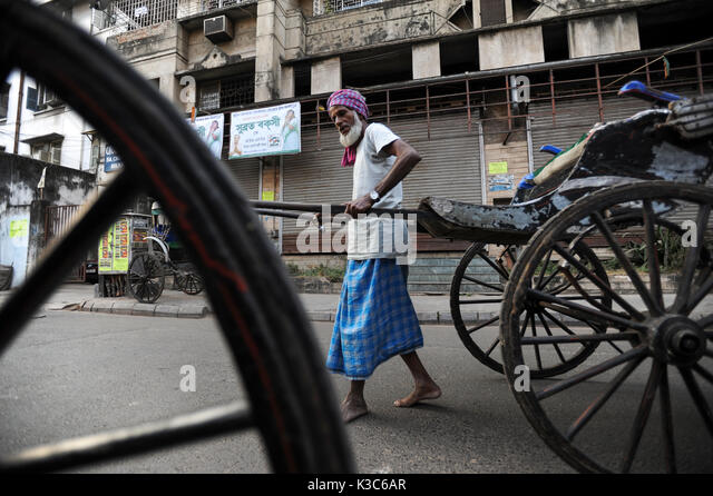 03.12.2011, Kolkata, West Bengal, India, Asia - Rickshaw puller Mohamed pulls his wooden rickshaw through the streets - Stock Image