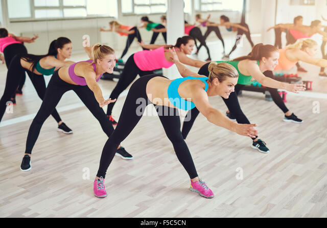 fitness, sport, training, gym and lifestyle concept - group of women working out in gym - Stock Image