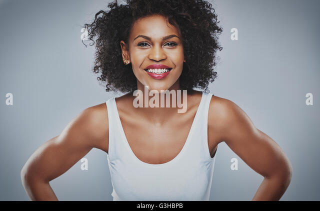 Front centered view on smiling female with enthusiastic expression leaning forward over gray background - Stock Image