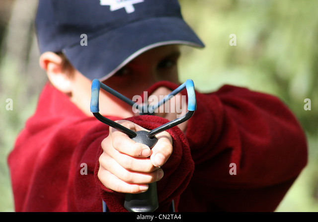 Boy with his sling shot poised for action; photographed at Prelude Lake, Yellowknife, Northwest Territories - Stock Image