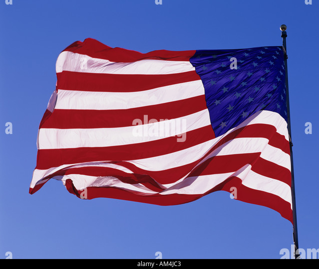 American Flag Stars and Stripes backlit waving in the wind with blue sky sunset Seattle Washington USA - Stock Image