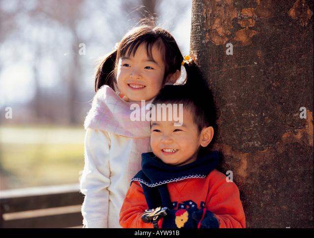Girl with her brother standing by a tree - Stock-Bilder