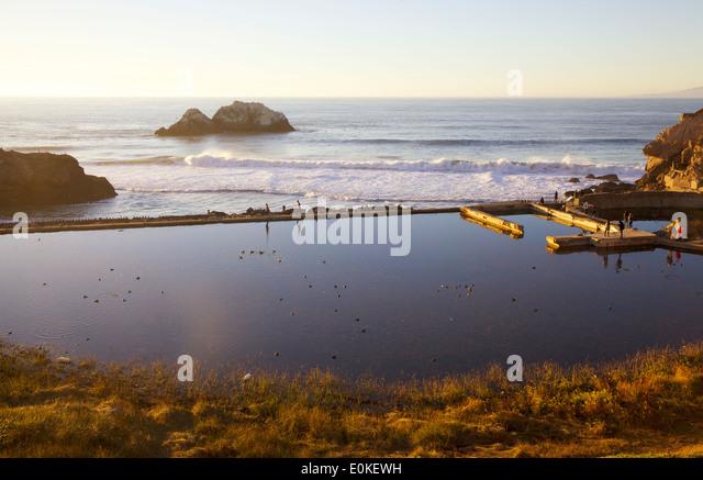People walk along the sea wall at the Sutro Bath Ruins at Lands End in San Francisco, California. - Stock Image