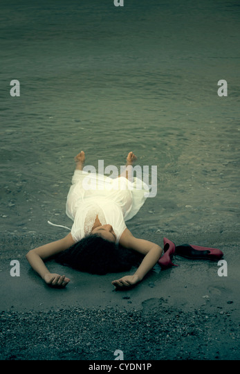 a woman is lying in the water, red shoes are next to her - Stock Image