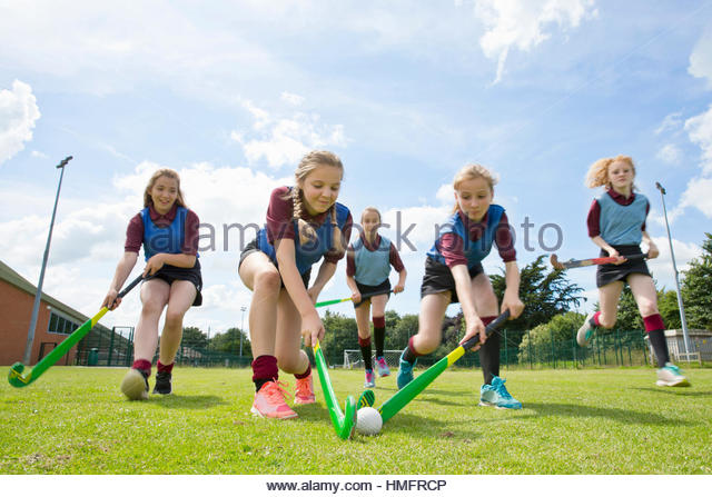 Middle schoolgirls running playing field hockey in physical education class - Stock-Bilder