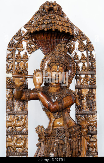 Ornate wooden carved krishna statue.  Worshiped hindu Indian deity - Stock Image