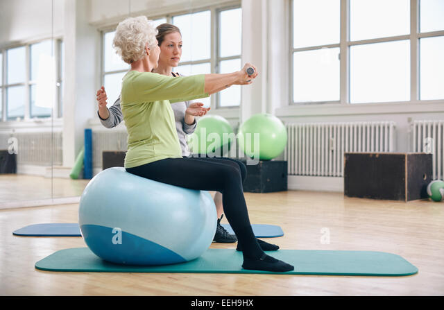 Female trainer assisting senior woman lifting weights in gym. Senior woman sitting on pilates ball doing weight - Stock Image