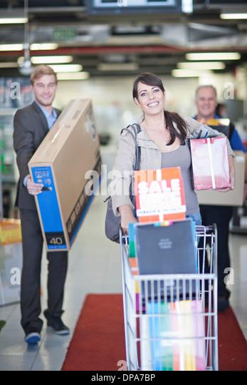 Woman leaving showroom with abundance of purchases - Stock-Bilder