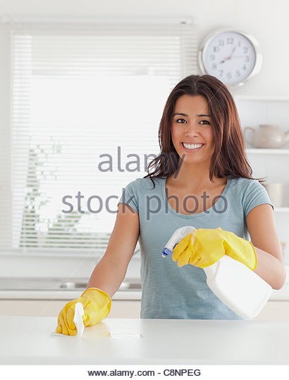 Charming female doing the housework while using a spray - Stock Image