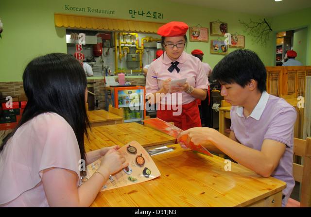 Singapore Orchard Road Plaza Singapura shopping mall complex restaurant Asian woman waitress job man couple table - Stock Image
