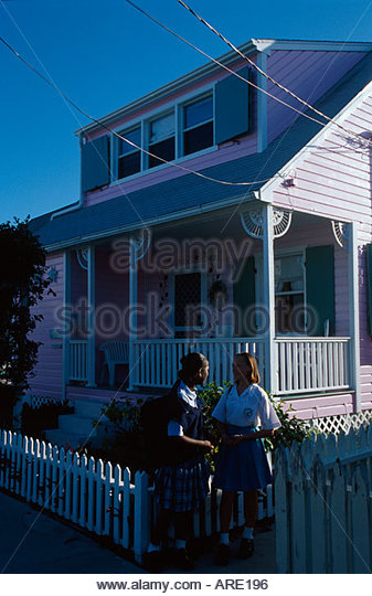 Bahamas Elbow Cay Hope Town students in school uniform picket fence pink house - Stock Image