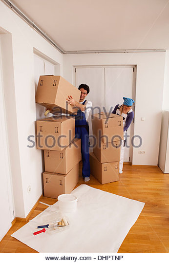 young couple new home unpacking moving in boxes - Stock Image