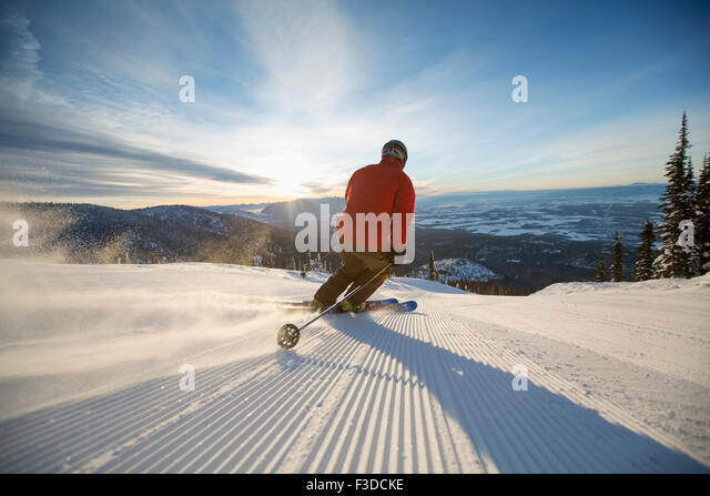 Mature man on ski slope at sunset - Stock Image