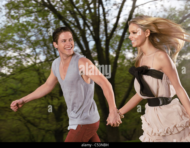 Young happy romantic couple running together holding their hands - Stock-Bilder