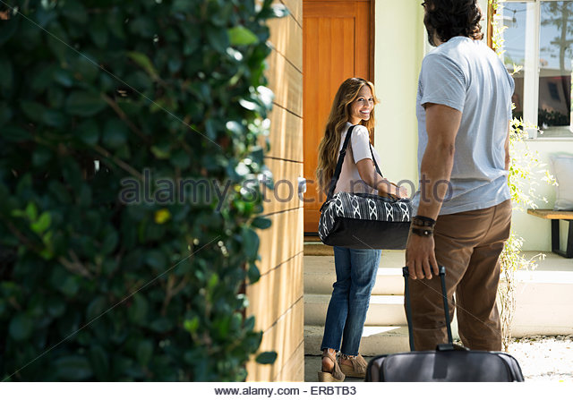 Couple with luggage arriving at vacation house - Stock Image