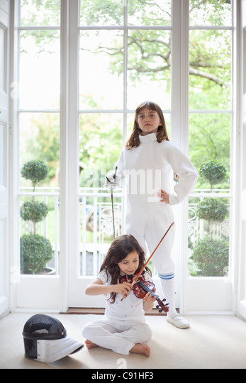 Girls with violin and fencing gear - Stock Image