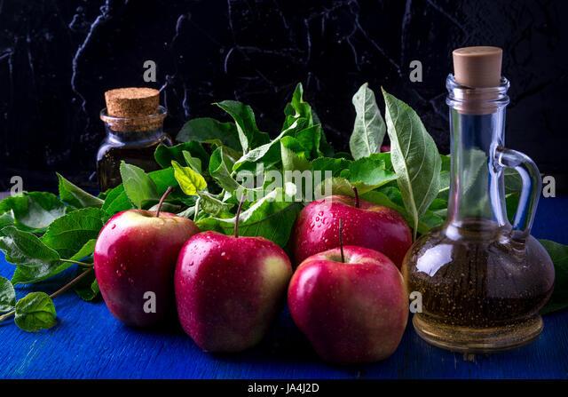 Apple cider vinegar. Three glass bottle on blue background. Red apples - Stock Image