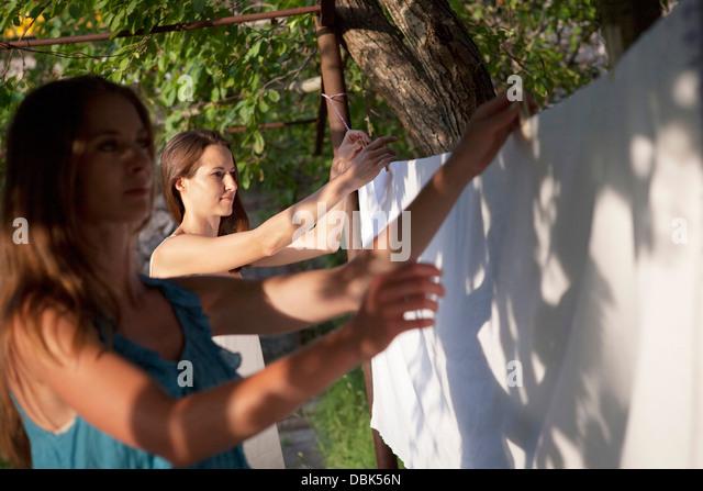 Two Young Women Hanging Laundry On Clothesline, Croatia, Dalmatia, Europe - Stock-Bilder