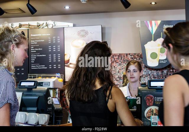 Madrid Spain Europe Spanish Plaza de Atocha Starbucks Coffee inside Hispanic woman employee barista cashier job - Stock Image