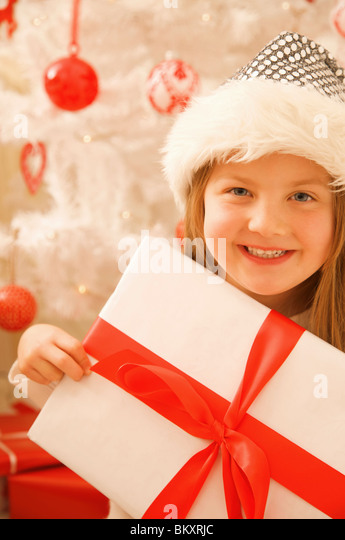 Close up of a smiling girl in a furry hat holding Christmas gift - Stock Image